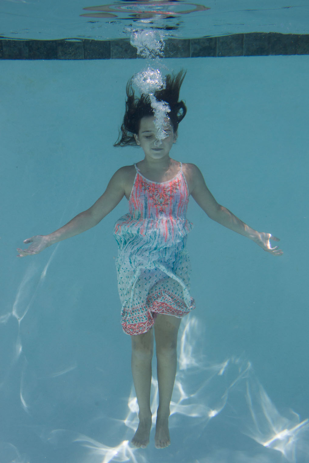 Bella with her arms outstretched standing in the pool